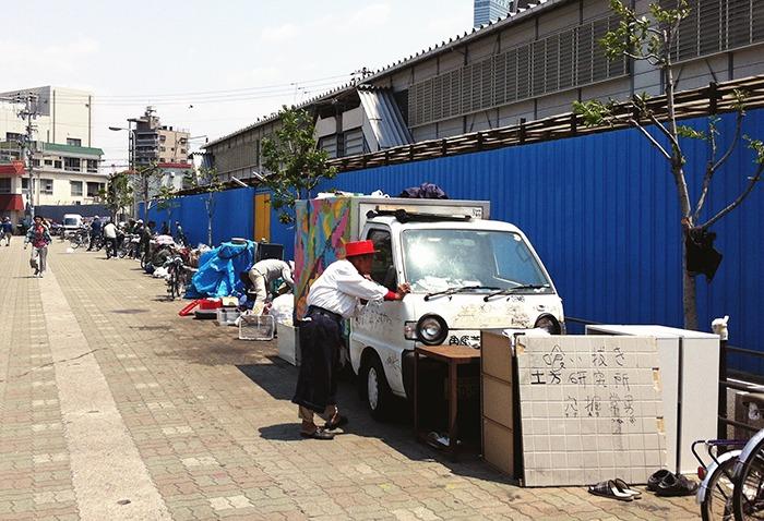 Vecino de Nishinari afeitándose en su coche-casa con la ayuda del retrovisor